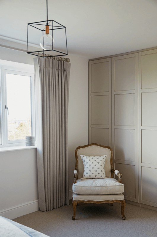 Triple French pleat curtains, contemporary metal ceiling light, Louis chair in cream linen