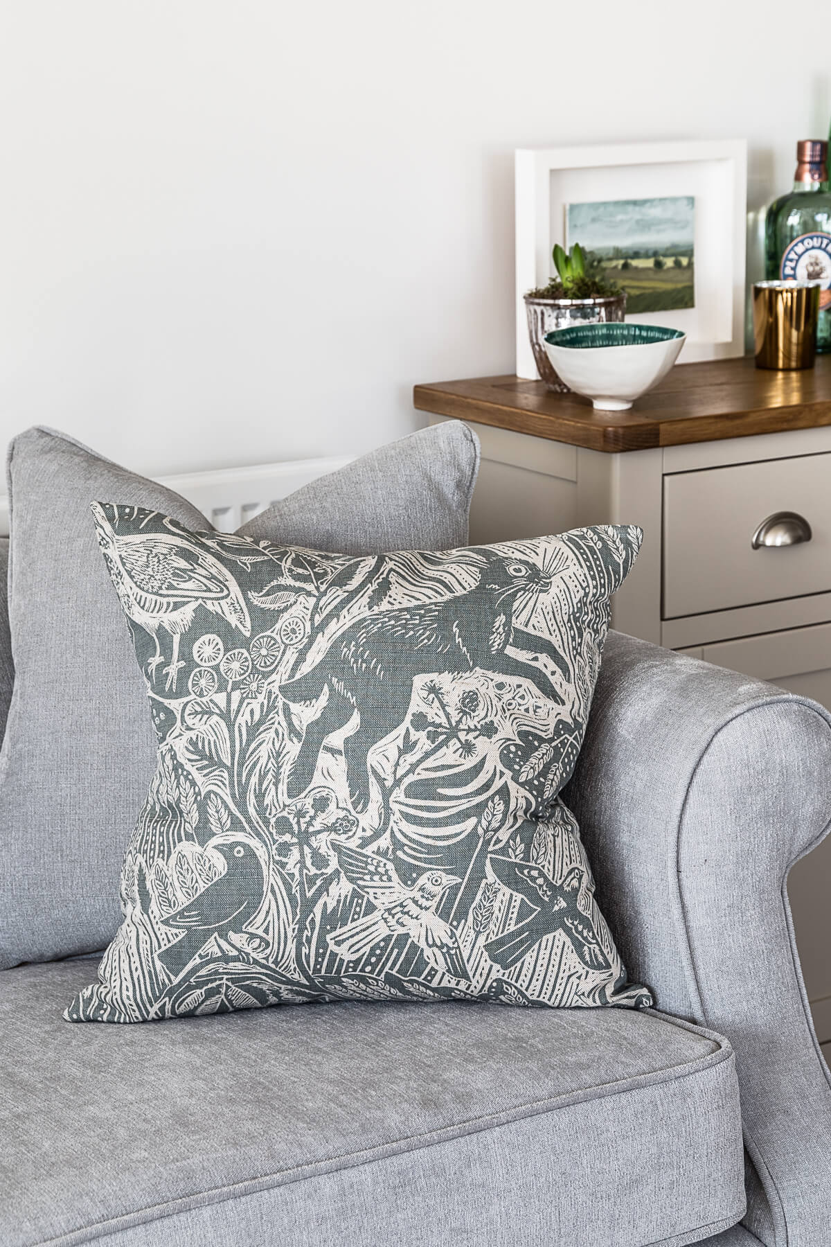 Contemporary country sitting room with cushion in Mark Hearld fabric