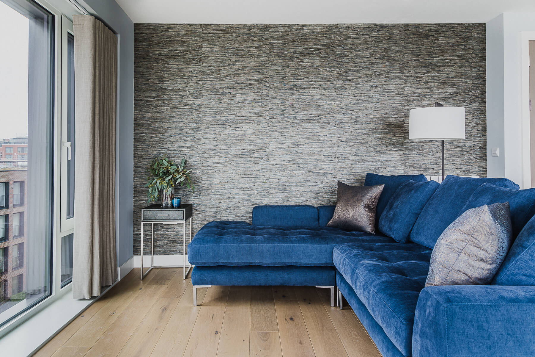 Royal Arsenal Woolwich Living area with textured wallcovering and blue sectional sofa with linen curtain