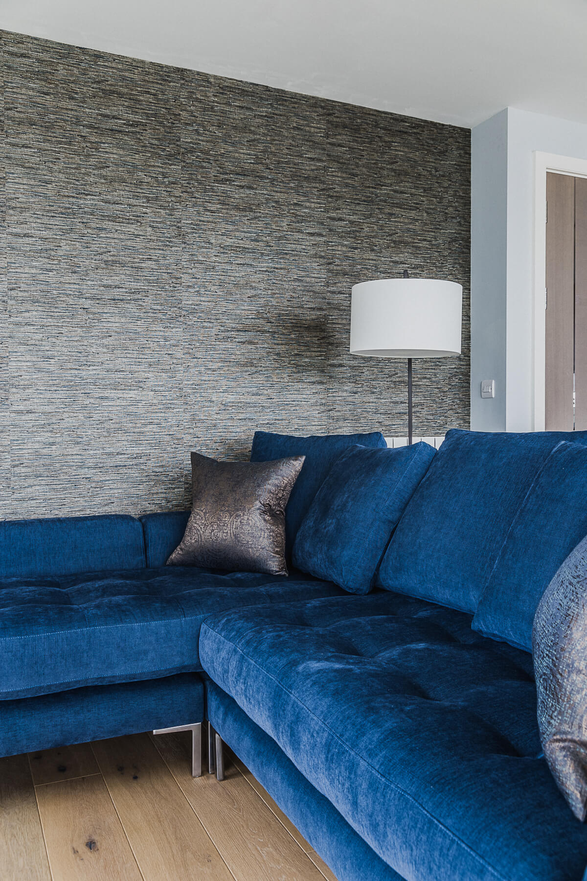 Royal Arsenal Woolwich Living area with textured wallcovering and blue sectional sofa