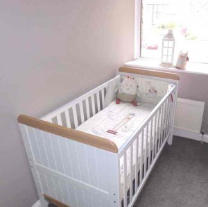 Warm, neutral nursery with white cot